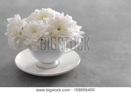 Bouquet of white chrysanthemum in cup on table