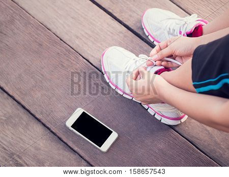 Closeup portrait of young woman runner tying her shoelaces with smartphone blank screen on wooden floor background.