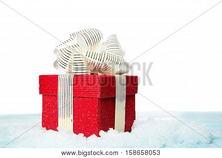 Red gift box on snow on white background