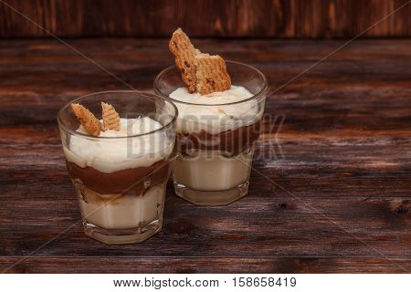 Vanilla and chocolate pudding dessert with a cream filled sandwich cookie. Dark wooden background