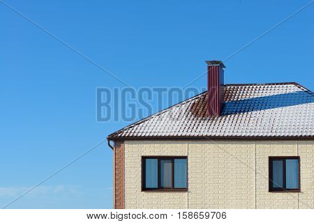 roof cottage with snow against the blue sky with blank place