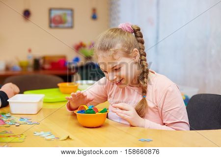 Cute Happy Girl With Disability Develops The Fine Motor Skills At Rehabilitation Center For Kids Wit