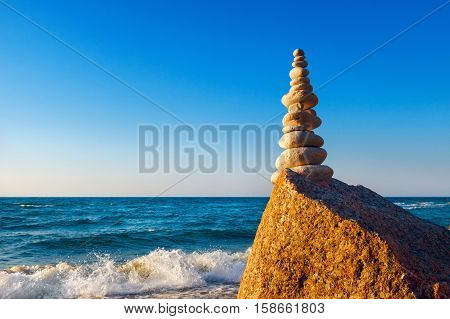 Concept of harmony and balance. high pyramid of white stones on the edge of a cliff. Rock Zen at sunset