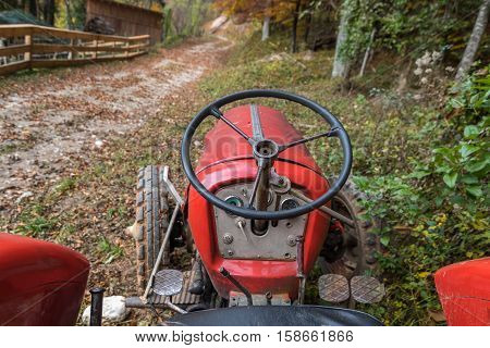 Driver's view from an old agricultural tractor in autumnal forest