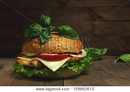 Delicious hamburger with cheese, tomatoes and basil  on wooden background. Fastfood meal. Vintage toned