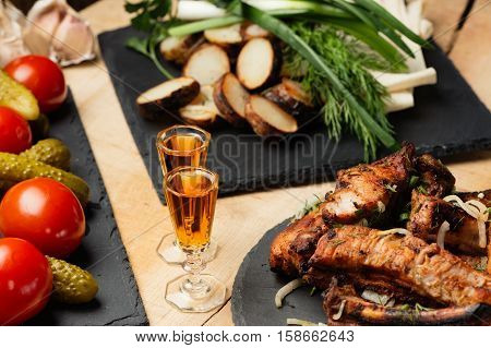 Fried meat, potatoes, greens, vegetables on black slate plates and two shot glasses with cognac in style a rustic