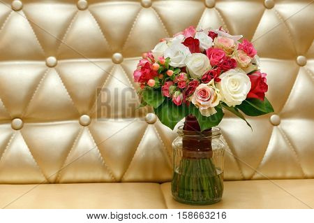 beautiful wedding bouquet from white and red roses on a gold background. bride's bouquet