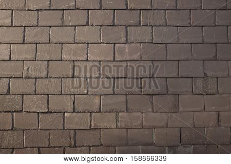 An old slate wall with a regular alternate patterned design.