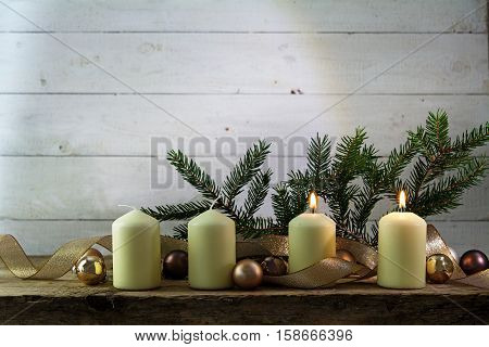 two white burning candles on the second advent christmas decoration with spruce twigs baubles and a golden ribbon on a rustic wooden board against white wood with copy space