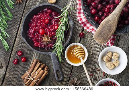 Fresh homemade cranberry sauce in a pan on dark wooden background with scattering of ripe berries. Top veiw