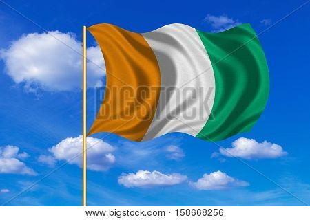 Cote D Ivoire national official flag. African patriotic symbol banner element background. Correct colors. Flag of Ivory Coast on flagpole waving in the wind blue sky background. Fabric texture. 3D rendered illustration