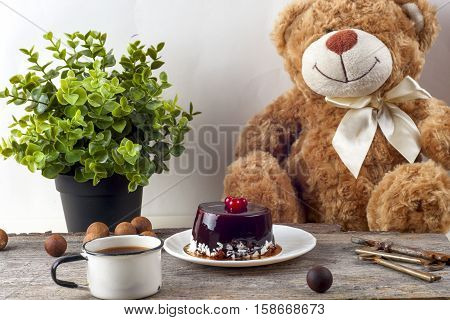 Festive tea party. Happy birthday cake with cup of tea and Teddy Bear