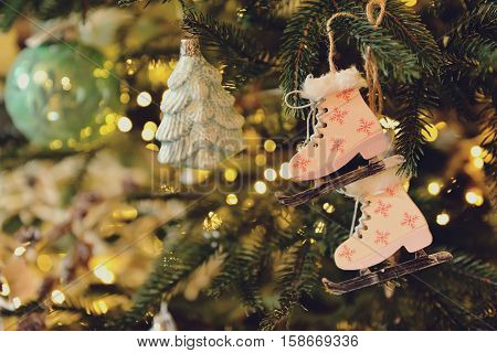 Toned image of christmas and New Year background with Eve Tree and decorations. Wooden handmade skates as toy for holiday fur tree.