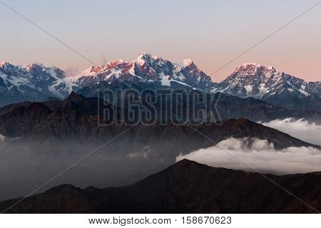 Dramatic Landscape With Snowy Peaks Rising Above Brown Hills And Morning Clouds. Dramatic Sunrise La