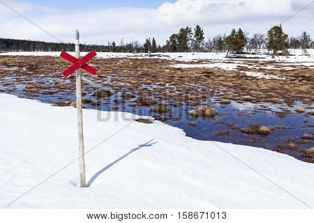 Closeup on a Snowmobile sign, red cross and trail in springtime. Snow, tussock and water in the mountains.