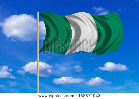 Nigerian national official flag. African patriotic symbol banner element background. Correct colors. Flag of Nigeria on flagpole waving in the wind blue sky background. Fabric texture. 3D rendered illustration