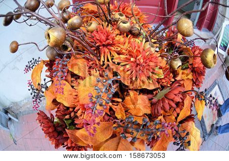 A bouquet of orange fall flowers, nuts, and berries