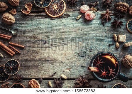 Mulled wine in rustic mug with spices and ingredients on wooden background. Top view flat lay. Retro styled photo. Copy space for your text.