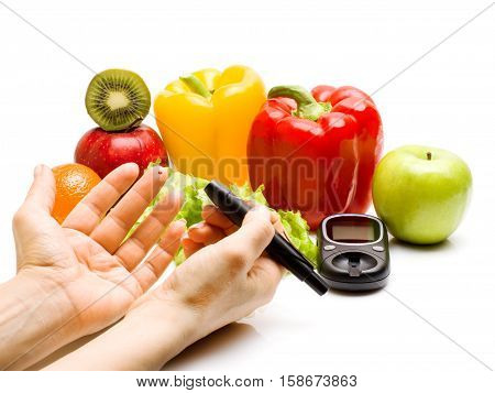 Glucometer in hand. fresh fruits, dumbbells for using in fitness, tape measure and glass of juice, concept for diabetes, slimming, healthy nutrition and strengthening immunity