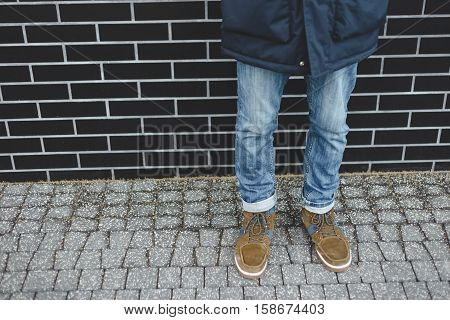 Men fashion, brown leather boots and blue jeans