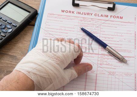 Worker Injured Hand Filling A Insurance Claim Form