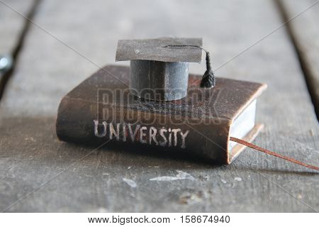 University Degree Concept. Vintage book with inscription and graduation cap