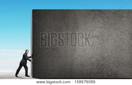 Young businessman making effort to move blank concrete wall