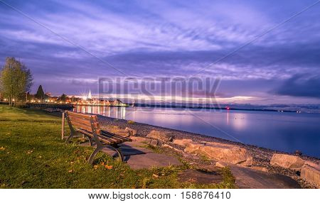 Wooden bench on a lake shore at sunrise - Colorful view over the Bodensee lake as the sun starts rising with a wooden bench on its shore. Image captured in Friedrichshafen Germany.