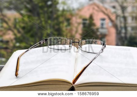 Open book and glasses. View from the window. Reading, learning books.