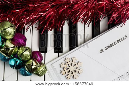 Christmas music concept. Printed music on the piano with jingle bells snowflake and spangle.
