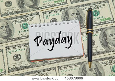 Notebook page with text PAYDAY on dollar background