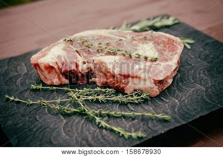 Raw rib eye steak with herbs on wooden board, toned image