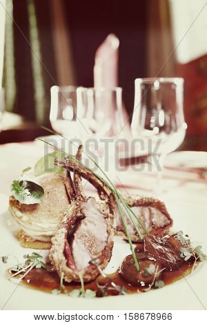 Rack of lamb with caramelized onions and homemade bun on restaurant table, toned