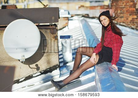 Young beautiful long-haired brunette girl sitting on the roof and squints from the bright sun. The wind ruffles her hair.