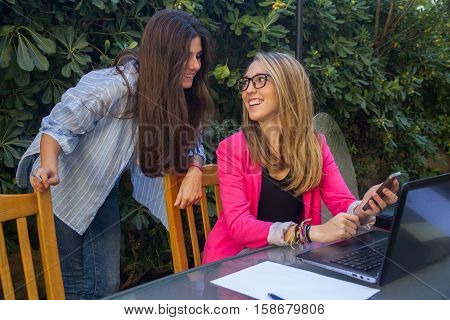 Young entrepreneurs working with a laptop. They are two beautiful Caucasian girls who are creating their company. They work on the terrace of their house.