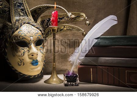 Vintage still life with old books near inkstand feather venezian mask and burning red candle in candlestick on canvas background.