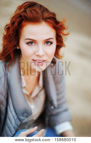 portrait of a beautiful young girl with flaming Auburn hair posing in the city streets clear autumn day....