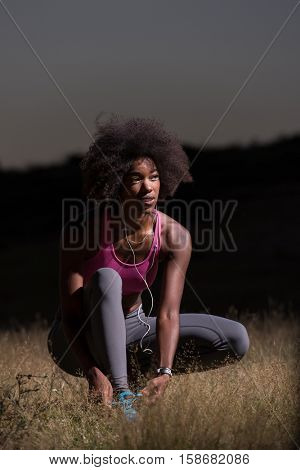 young African american woman runner tightening shoe lace in nature  Fitness, people and healthy lifestyle