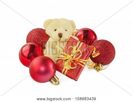 Teddy bear classic soft toy sitting with gift box and surrounded by red Christmas balls isolated over white. Front view. Christmas and New Year theme.