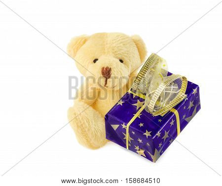 Teddy bear classic soft toy sitting with blue gift box isolated over white. Front view.