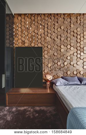 Modern style bedroom with a burgundy carpet on the floor. There is a bed with pillows and a coverlet, a design lamp, a black locker. Back wall has wooden textures. Vertical.