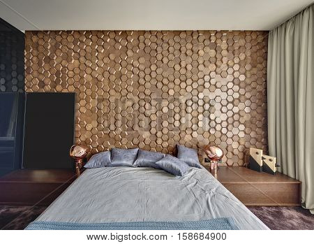 Contemporary bedroom with a burgundy carpet on the floor. There is a bed with pillows and a coverlet, wooden rack with design lamps and decorations in a form of birds. Back wall has wooden textures.
