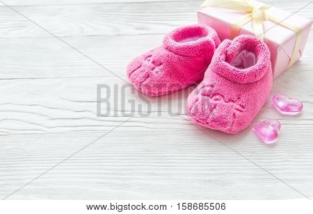 pink baby's bootees on wooden background close up