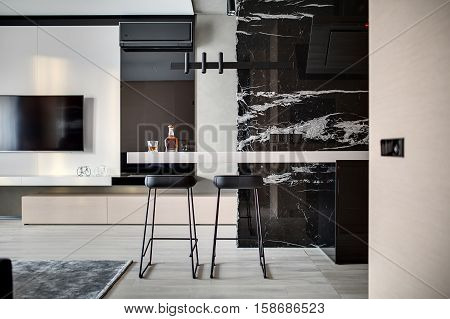 Contemporary hall with a parquet on the floor. There is a black marble wall with kitchen hood, tabletop with a bottle and glass, stools, wooden lockers, TV, fireplace, conditioner and decorations.
