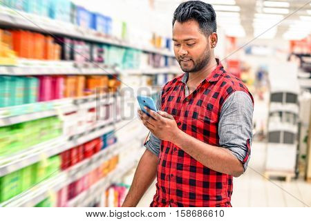 Young indian man using mobile in blurred store lane - Handsome happy guy holding smart phone and smiling inside shopping mall next to colorful bottles