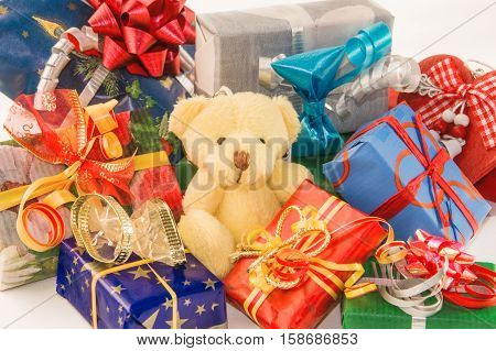 Teddy bear classic soft toy sitting with heap of gift boxes. For Christmas New Year birthday wedding anniversary etc. Horizontal.