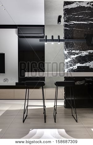 Black marble wall with white patterns with a light tabletop and two black stools under it. There are glowing lamps, white wall with a TV, decorations, black fireplace with conditioner, wooden lockers.