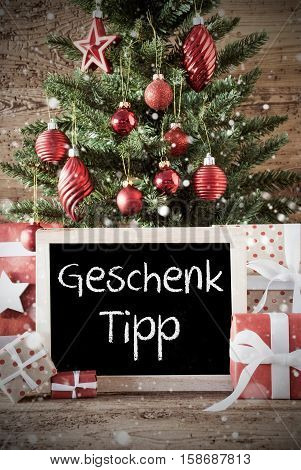 Chalkboard With German Text Geschenk Tipp Means Gift Tip. Nostalgic Christmas Card For Seasons Greetings. Christmas Tree With Balls. Gifts Or Presents In The Front Of Wooden Background.