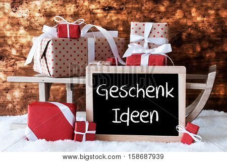 Chalkboard With German Text Geschenk Ideen Means Gift Ideas. Sled With Christmas And Winter Decoration. Gifts And Presents On Snow With Wooden Background And Bokeh Effect.