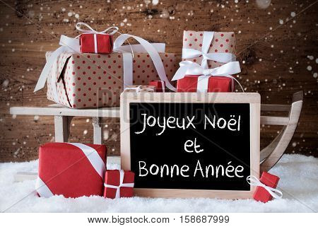 Chalkboard With French Text Joyeux Noel Et Bonne Annee Means Merry Christmas And Happy New Year. Sled With Christmas And Winter Decoration And Snowflakes. Presents On Snow With Wooden Background.